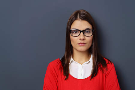 Serious unimpressed woman in glasses staring straight ahead at the camera with a deadpan expression, over grey with copy space