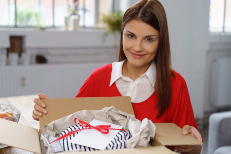packet: Smiling woman displaying her online order gift wrapped in a brown cardboard box as she unwraps it in her kitchen Stock Photo