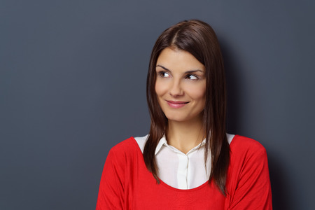 pretty brunette woman: Thoughtful attractive young woman gazing to the side towards blank copy space on a grey background with a happy smile