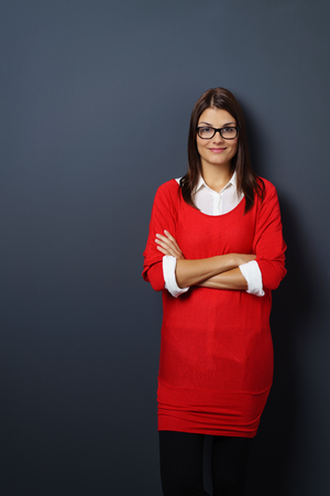 adult wall: Cute young adult female in red sweater with rolled up sleeves and folded arms standing in front of black wall