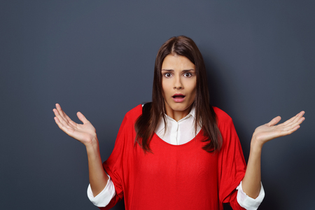 mujer decepcionada: Frustrated attractive young woman gesturing with her hands and her mouth agape, upper body on a grey background