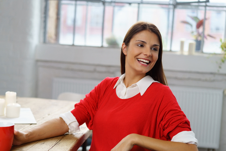 young woman sitting: Stylish vivacious young woman in a colorful red outfit sitting at a table relaxing at home with coffee looking over her shoulder with a laugh