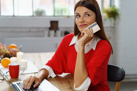 wry: Undecided young woman making a purchase online sitting at home at her laptop holding her bank card in her hand and looking up with a thoughtful expression and wry smile Stock Photo