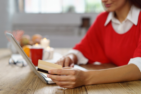 interior home: Housewife making an online purchase with her bank card as she relaxes at home at the dining table, close up focus to her hand and the card