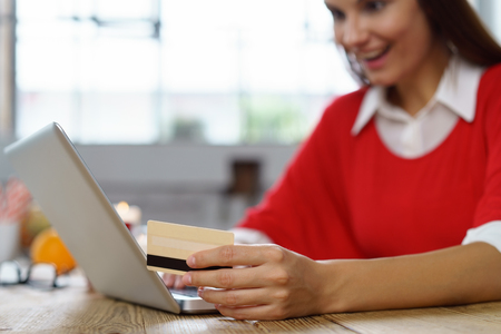 Young woman ordering or shopping online on her laptop computer holding a credit card in her hand, close up focus to her hand Stock Photo