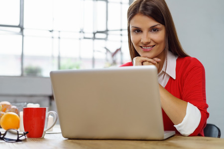 website window: Sincere interested young woman with a warm friendly smile resting her chin on her hands looking at the camera over her laptop as she works from home in the kitchen
