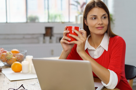 Young woman pausing for a cup of coffee sitting at her laptop computer in the kitchen looking to the side with an observant smile
