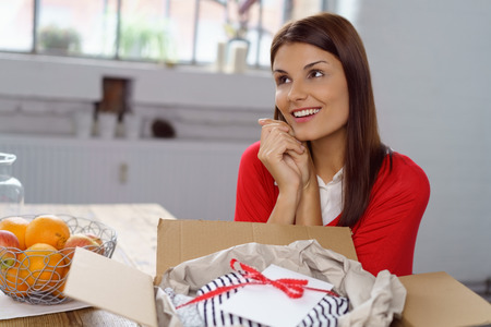 blissful: Romantic young woman unwrapping a gift from her sweetheart sitting in front of the open carton with a blissful smile looking up into the air