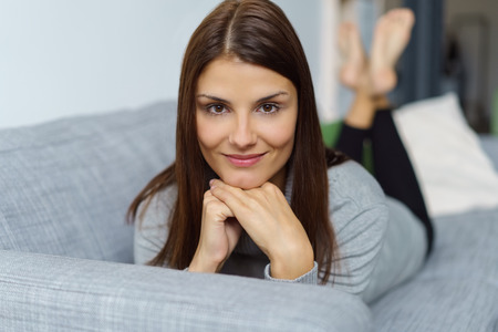 pretty brunette woman: Pretty brunette woman with a lovely warm friendly smile relaxing on her stomach on a sofa at home