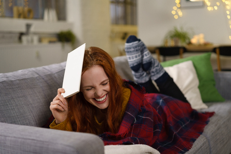 long socks: woman lying in the sofa laughing and holding a book on her head Stock Photo