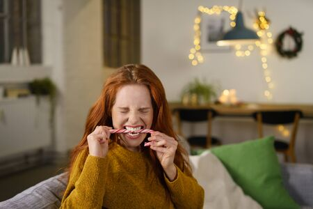 funny face of an attractive young woman biting a festive candy cane symbolic of Christmas and the holiday season