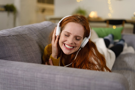 Pretty young woman listening to her music on a set of stereo headphones as she relaxes on the sofa with a beaming smile of pleasure
