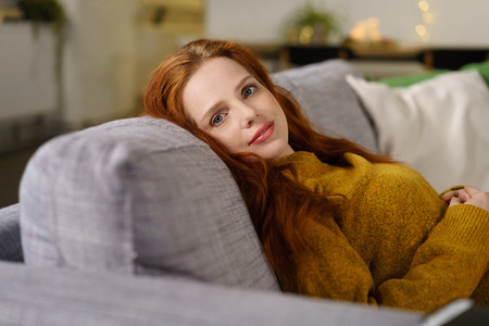 long weekend: serene young woman with long red hair relaxing at home Stock Photo