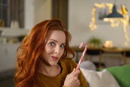 pensive woman holding a candy cane in her hand while sitting on her sofa at home in christmas time Stock Photo