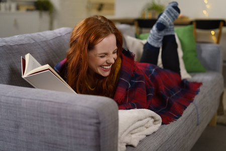 redhead woman laughing while reading a funny book Stock Photo