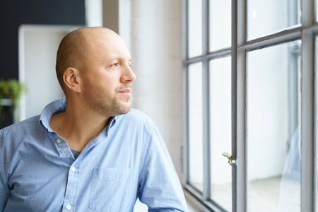casual men: Middle-aged man watching through a window with a thoughtful expression as he leans on the sill