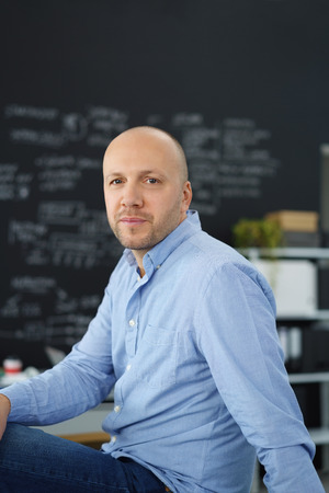 his shirt sleeves: Laid back relaxed businessman sitting on his desk at the office in his shirt sleeves looking thoughtfully at the camera Stock Photo