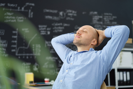 destress: Tired businessman taking a moment to de-stress leaning back in his chair with his hands behind his head and eyes closed Stock Photo