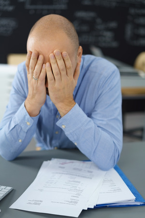 despondent: Despondent businessman covering his eyes with his hands as he sits at a desk in the office with a file and documents in front of him