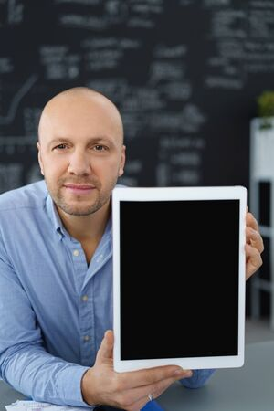 slight: Businessman giving a presentation displaying a tablet with a blank black screen to the camera with a slight smile