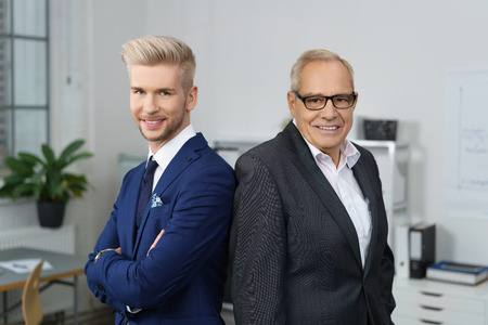 Confident successful business partners posing together with a stylish young man and his older mentor standing back to back smiling at the camera
