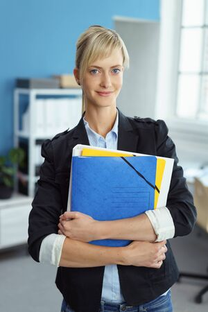 Attractive modern secretary or personal assistant in a blazer standing with a bundle of office file clasped in her arms smiling at the camera