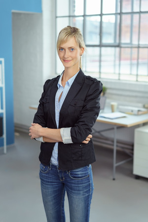 informal clothes: Tall thin businesswoman in informal clothes standing with folded arms in the office smiling at the camera