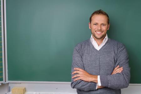 Gut aussehende Dozenten oder Lehrer mit einem zuversichtlich Lächeln mit gefalteten Armen vor einer leeren Tafel in einem Klassenzimmer stehend Standard-Bild - 67339050
