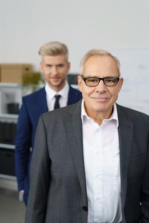Senior business executive met zijn jongere werknemer die achter hem in het kantoor Stockfoto - 68433263