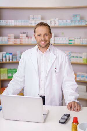 medical man: Smiling confident male pharmacist in the pharmacy standing at a counter in front of laden shelves at a laptop computer smiling at the camera Stock Photo