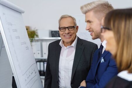 strategy meeting: Experienced business team holding a meeting standing in front of a flip chart planning and analysing their strategy with focus to an older man