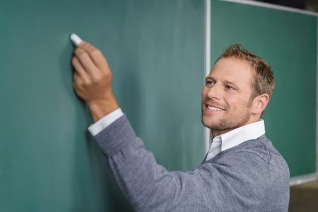Leraar of spreker die op een bord met zijn linkerhand schrijven opgevoed met krijt en exemplaarruimte voor uw bericht, hoekige mening