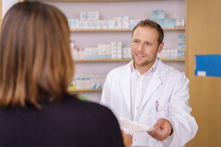 Attraktive männliche Apotheker einen Kunden hält ein Rezept für Medikamente in der Hand dienen, als er ihr eine Frage stellt,