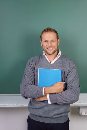 Smiling confident teacher or businessman standing in front of a chalkboard clasping a file in his arms smiling at the start of a presentation