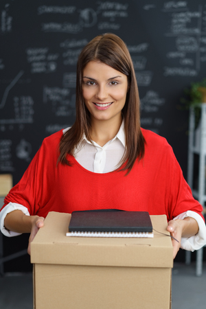 Young woman carrying a brown cardboard box and file in the office standing looking at the camera with a friendly smile