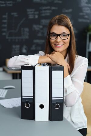 Attractive young business secretary wearing glasses sitting at her desk leaning on three large upright office binders with blank labels Stock Photo