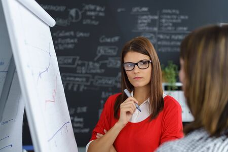 criticism: Two young businesswoman in a meeting standing together in front of a flip chart having a serious discussion