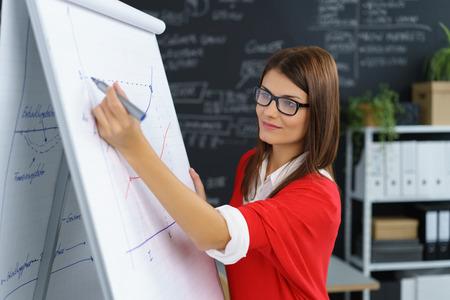 Jeune femme d'affaires travaillant sur un tableau de dessiner un graphe de performance comme elle prévoit ou analyse un projet Banque d'images