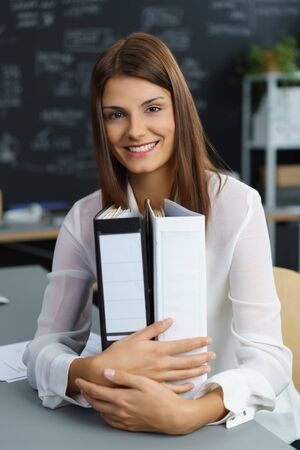 Contented young businesswoman with two large office binders with blank labels clasped in her hands smiling happily at the camera Stock Photo
