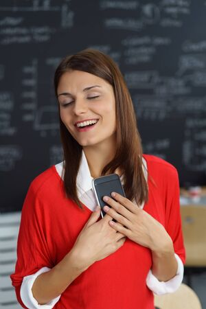 Delighted young businesswoman smiling with bliss as she stands in the office clutching her mobile phone to her heart with her eyes closed