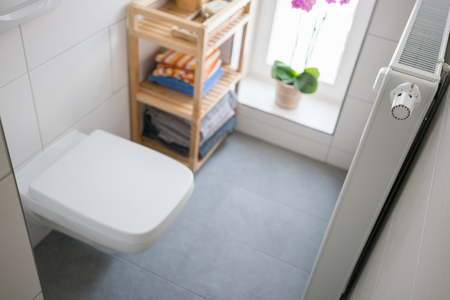 wall mounted: Compact bathroom interior with modern wall mounted toilet and fresh linen displayed on a wooden rack alongside a radiator Stock Photo