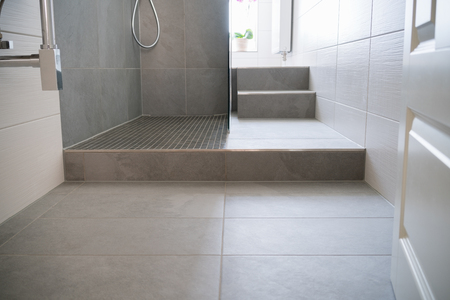 shower cubicle: Tiled floor and step into a glass fronted modern shower cubicle in a neutral toned monochrome bathroom