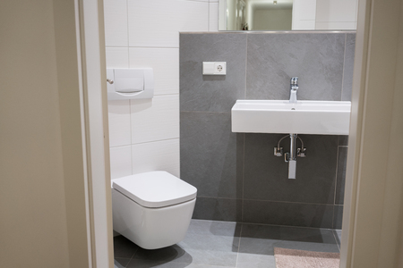 Modern compact luxury tiled bathroom with rectangular plumbing fittings and neutral decor viewed through a doorway Stock Photo