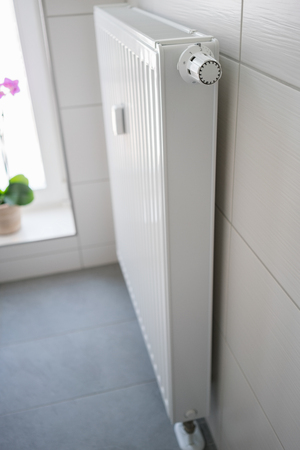 wall mounted: Modern wall mounted white radiator with thermostat control in a tiled bathroom, close up end view