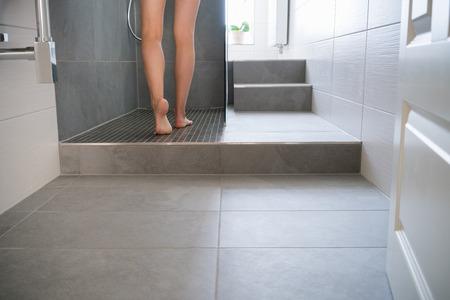 현대 타일 된 욕실에서 씻어 샤워 칸막이로 스테핑 젊은 여자의 벌거 벗은 다리의 낮은 각도보기