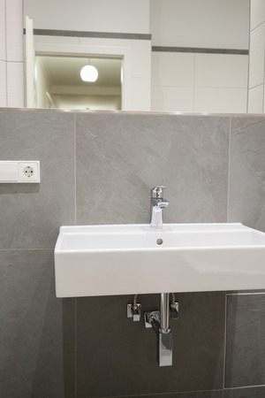 wall mounted: Wall mounted rectangular wash basin and electrical plug in a luxury tiled bathroom in a close up view
