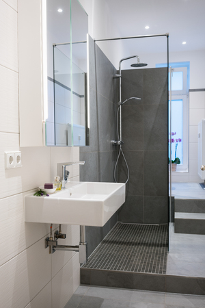 shower cubicle: Modern upmarket bathroom interior with a wall mounted rectangular hand basin, glass shower cubicle and tiled floors and walls in neutral tones Stock Photo
