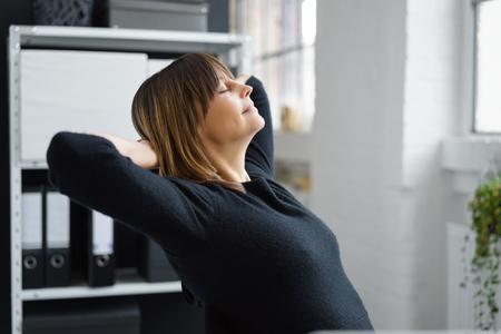 魅力的な女性実業家の休憩を取ってリラックスして目を閉じて、プロファイル表示彼女の椅子にもたれかかって、ストレス解消