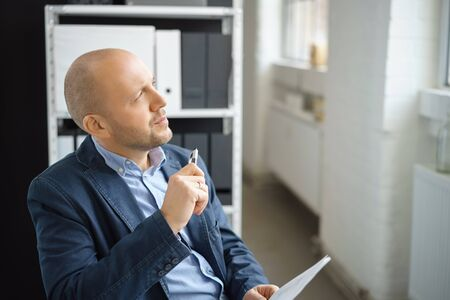 contemplates: Thoughtful businessman sitting staring through a window with a document in his hand as he contemplates his choices