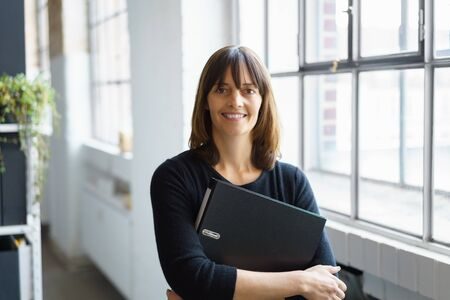 Smiling businesswoman holding a large black office binder clutched in her arms as she pauses alongside a bright window in the office